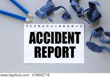 Accident Report. Text On White Notepad Paper. Near Torn Blue Paper
