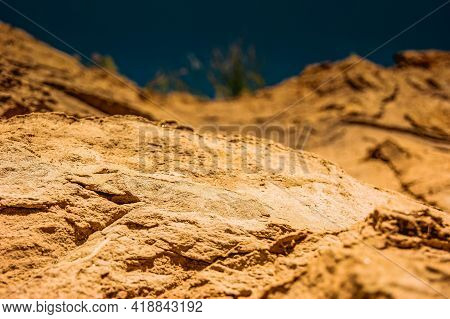 Sand Cliffs Against The Blue Sky. Bright Sand Texture. The Rough And Delicate Texture Goes To The Pa