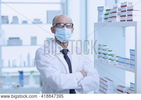 Pharmacist Is Working In Protective Mask. Man Wearing Special Medical Uniform. Located In Pharmacy.