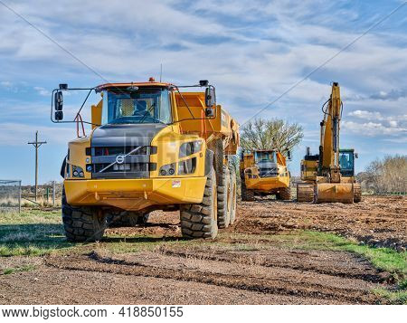 Fort Collins, CO, USA - April 28, 2021: Powerful Volvo A45G articulated dump haulers and CAT excavator on a construction site.