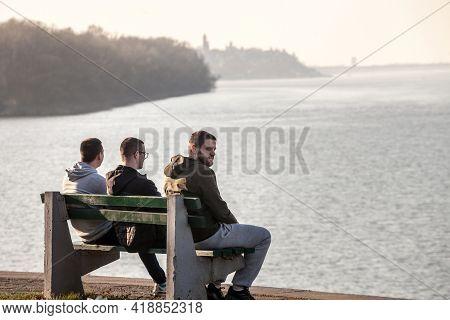 Belgrade, Serbia - March 13, 2021: Three Young Men, Serbs, Belgradians, Friends, Sitting On A Bench