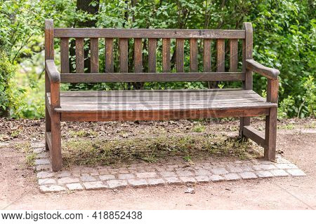 Old Wooden Bench. Cozy Bench In A Green Corner Near The Path. A Bench Under The Walls Of The Castle