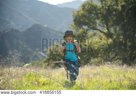 Kid With Backpack Hiking In Scenic Mountains. Boy Child Local Tourist Goes On A Local Hike.