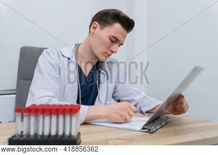 Professional Male Caucasian Doctor Medical Staff Read And Write On Document Report In Hospital Clini