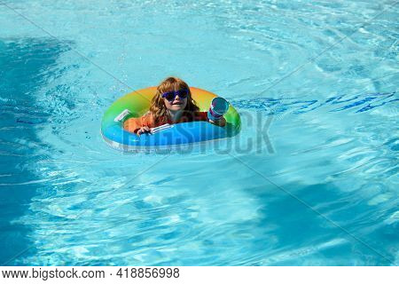 Child In Swimming Pool Playing In Water, Copy Space. Vacation And Traveling With Kids. Children Play