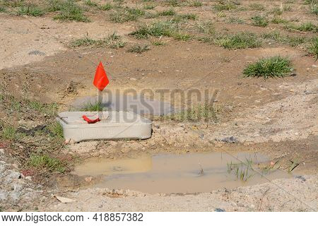 Red Flag Warning At Construction Site Marking Underground Lines Where Not To Dig