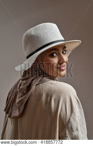 Portrait Of Happy Young Arabian Girl In Hijab And Hat Posing Backwards On Light Background And Looki