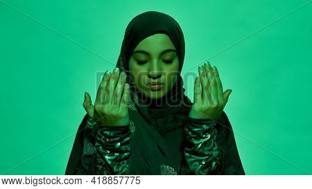 Young Arabian Girl In Dark Hijab With Closed Eyes Holding Bare Hands In Front Of Her Face On Light G