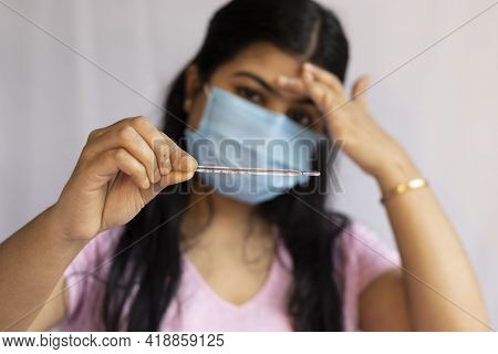 Selective Focus On An Analog Thermometer Held In Hand Of A Mid Adult Indian Woman Wearing Surgical N