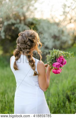 Back View Bride Walking With Bouquet Of Pions And Wearing White Dress.