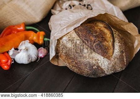 Crusty Sourdough Round Bread Made Of Whole Grain In Craft Package With Fresh Vegetables Aside. Natur