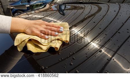 woman polishes the car, uses a microfiber cloth and polish to wipe the car's body with polish.