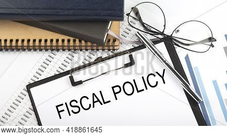 Text Fiscal Policy On Office Desk Table With Notebooks, Supplies,analysis Chart, On The White Backgr