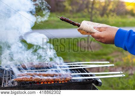 Cooking Delicious Turkish Adana Kebab On A Portable Charcoal Grill At A Picnic Location, Smoke And F