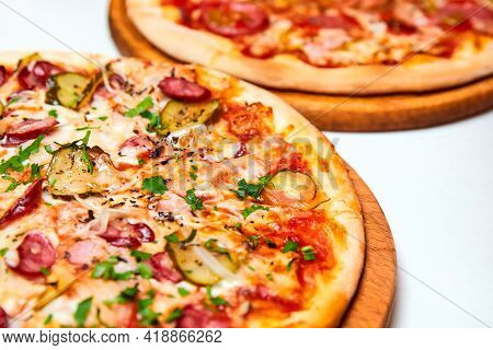 Pizza With Salami, Bell Pepper, Tomatoes And Cheese, Pickles, Bacon And Sausages On A Light Backgrou