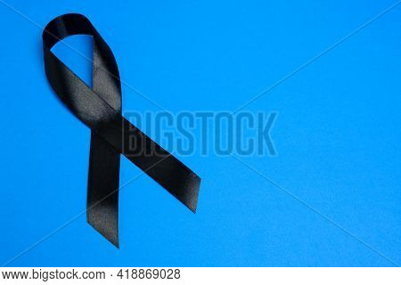 Black Ribbon On Blue Background Is Symbol Melanoma, Symbol Of Memory Victims Stalinism And Nazism An