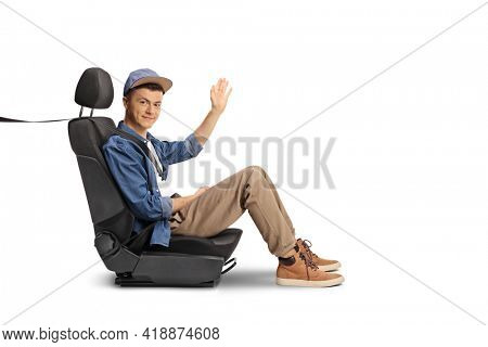 Guy sitting in a car seat with a seatbelt and waving isolated on white background