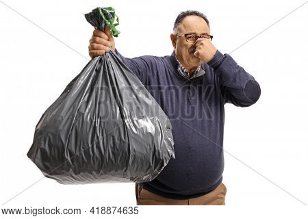 Mature man holding a smelly waste bag isolated on white background