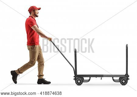 Delivery worker pushing an empty hand truck isolated on white background
