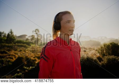 Female Athlete Listening To Music With Headphones Jogging In Luscious Forest