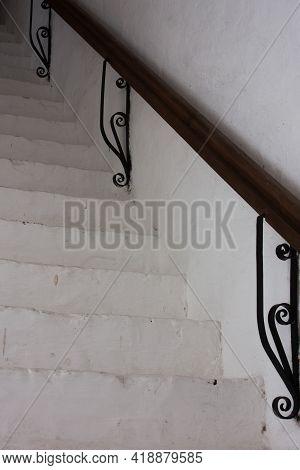 Steep White Stone Staircase Leading Upward, White Stone Wall And Dark Railing