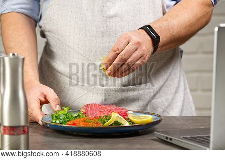 Cooking With Notebook Tuna Steak In Home Kitchen. Online Cooking Recipe Concept, Fish Cooking At Hom