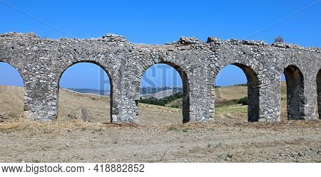 Long Ancient Roman Aqueduct That Runs In The Middle Of The Field Made With Arches And With The Right