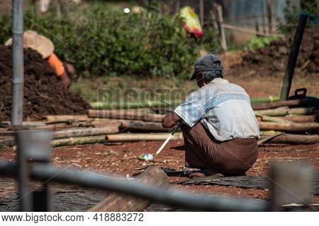 A Local Burmese Man In Traditional Longyi Sits In A Squat As He Cuts Bamboo, Shan State, Myanmar