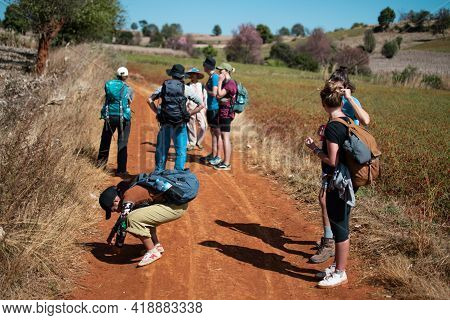 Shan State, Myanmar - January 6 2020: A Tourist Group With Backpacks Hikes On A Dirt Road By Chili F