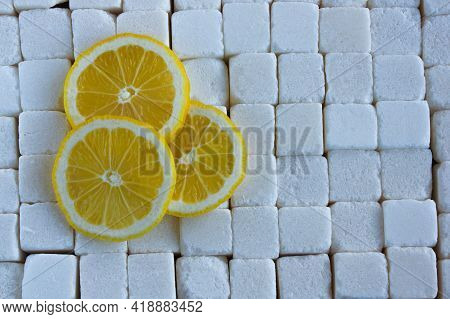 Lemon Slices On The Background Of Large Pieces Of Refined Sugar, The Concept Of Taste Contrast