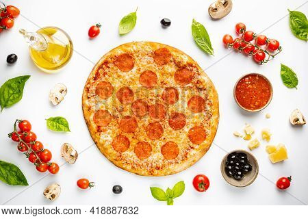 Tasty Pepperoni Pizza And Cooking Ingredients Tomatoes Basil On White Background. Top View Of Hot Pe