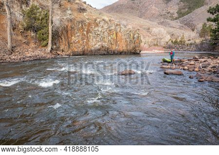kayaker with a whitewater inflatable kayak on a shore of mountain river in early spring - Poudre River in northern Colorado, low angle aerial view
