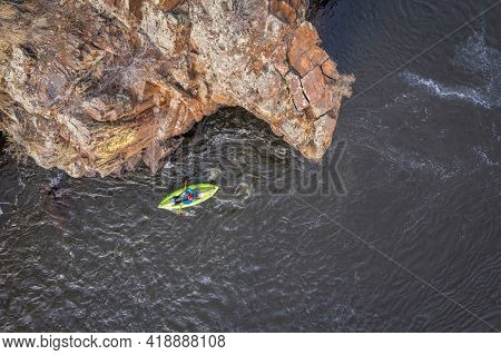paddling a whitewater inflatable kayak on a mountain river in early spring - Poudre River in northern Colorado, aerial view
