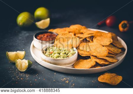 Single Big White Plate Of Yellow Corn Tortilla Nachos Chips With Salsa And Guacamole Sauce Over Dark