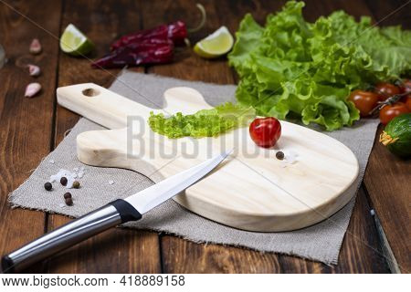 A Cutting Board In The Form Of A Guitar On A Wooden Table. Handmade Chopping Board. Fresh Tomatoes,