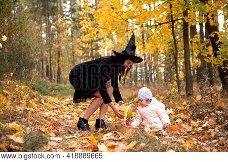 Woman Witch Plays With A Small Child In The Autumn Forest. Halloween Concept Costumes. Witch And Bun