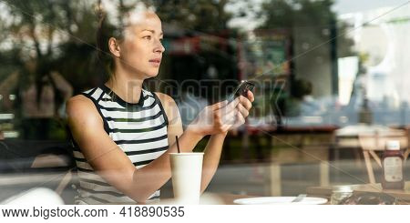 Thoughtful Caucasian Woman Holding Mobile Phone While Looking Through The Coffee Shop Window During