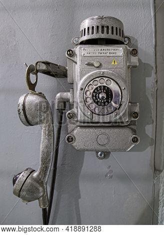 Old metal wall-mounted telephone with rotary dial. Text translation: When calling the dispatcher, push the lever down. Antique phone with dial