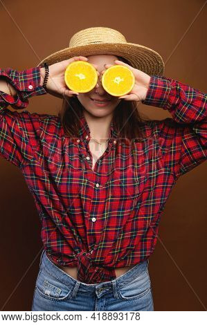 Smiling Woman Hold Halves Of An Orange In Her Hands Instead Of Eyes. Straw Hat, Plaid Shirt, Studio