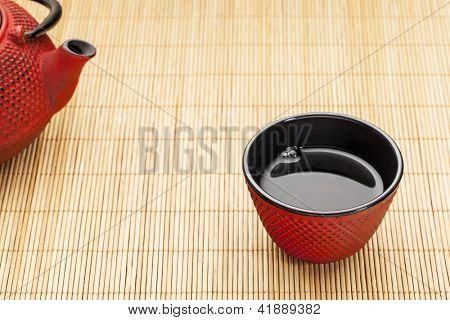 Japanese cup of tea with a tetsubin on a bamboo mat - a traditional cast iron red hobnail design with black enamel inside