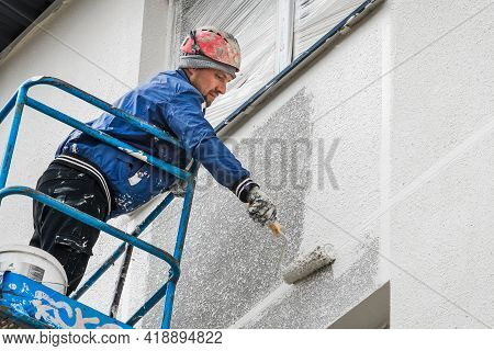 Belarus, Minsk - May 28, 2020: Worker On A Lifting Platform Painting A New Facade Of A House Under C