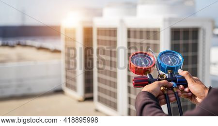 Air Repair Mechanic Using Measuring Equipment For Filling Industrial Factory Air Conditioners And Ch