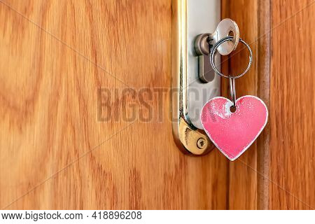 Close-up And Selective Focus Of A Red Worn Metal Heart-shaped Keychain On The Key In The Door Lock.