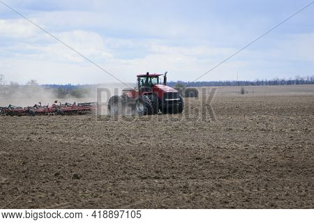 Red Tractor With A Plow On An Agricultural Field. Work In The Field With A Big Tractor. Modern Red T