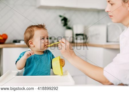 A Young Mother Feeds Her Young Son, Who Is Sitting In A High Baby Feeding Chair. Care, Motherhood, C