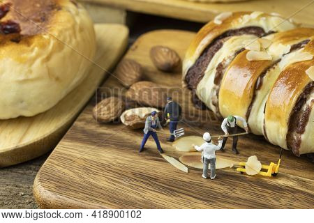 Miniature Chef Is Urging The Miniature Workers To Make Bread On Wooden Tray.