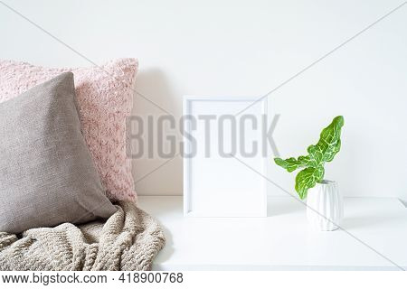 Empty White Frame Mockup On White Table. Soft Colored Cushions, Plaid And White Vase With An Arum It