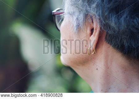 Side View Of The Face Of A Senior Woman Wearing A Golden Earring. Concept Of Old People And Accessor