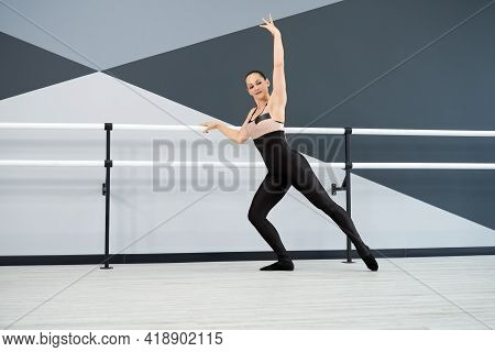 Graceful Woman Wearing Clack Tight Outfit Practicing Dance Move With Hand Up, Holding Handrails In B