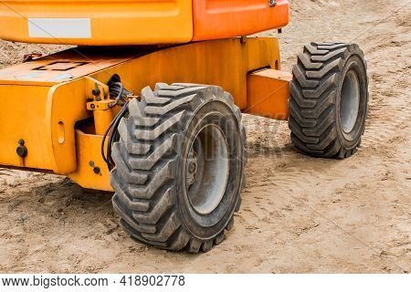 Wheels Of Industrial Lifting Transport Tire Truck Against The Background Of Sand At A Construction S